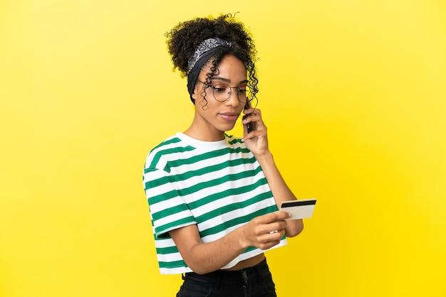 Молодая афро-американская женщина, изолированная на желтом фоне, покупает с мобильного телефона с помощью кредитной карты