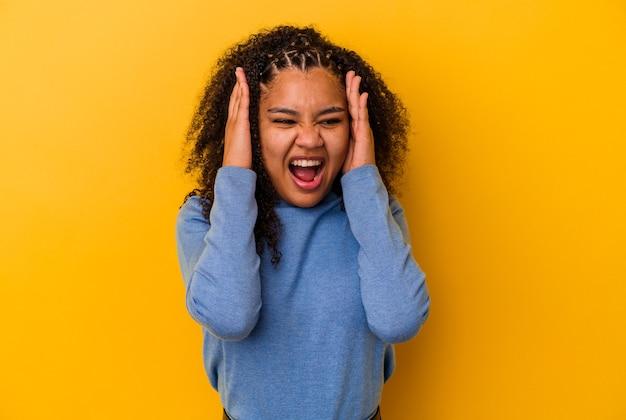 大きな音を聞かないように手で耳を覆う黄色の背景に若いアフリカ系アメリカ人女性。