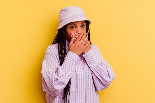 걱정 찾고 손으로 입을 덮고 노란색 배경에 고립 된 젊은 아프리카 계 미국인 여자.