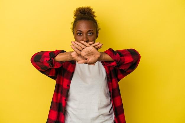 Молодая афро-американская женщина, изолированная на желтом фоне, делает жест отрицания