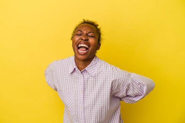 黄色の背景に分離された若いアフリカ系アメリカ人の女性は、面白いとフレンドリーな舌を突き出しています。