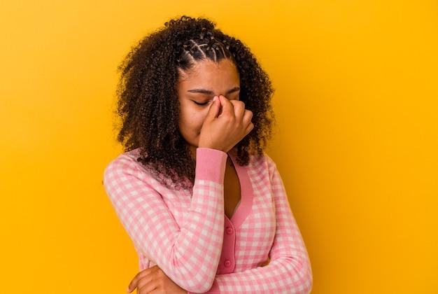 黄色い背景にアフリカ系アメリカ人の若い女性が頭が痛く、顔の前に触れている。