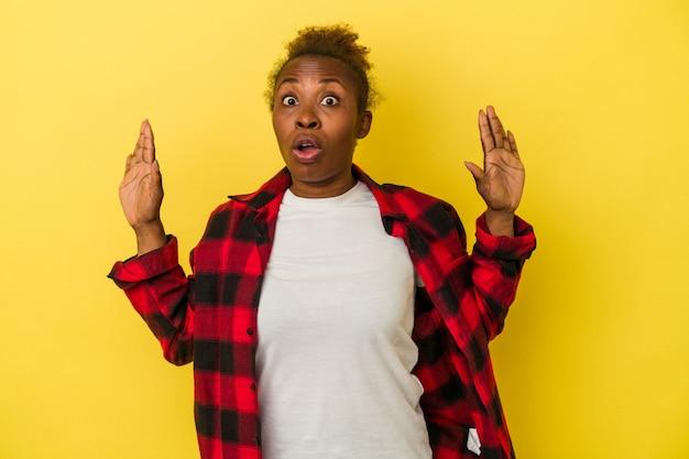 アイデア、インスピレーションの概念を持つ黄色の背景に分離された若いアフリカ系アメリカ人女性。