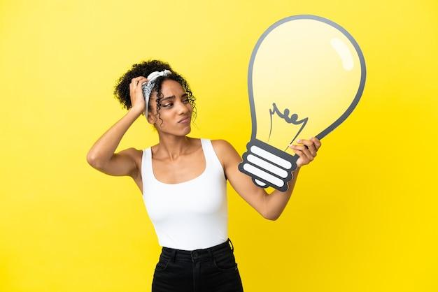 Молодая афро-американская женщина, изолированная на желтом фоне, держит значок лампочки и сомневается