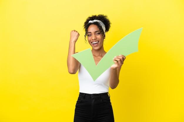 Молодая афро-американская женщина, изолированная на желтом фоне, держит значок галочки и празднует победу