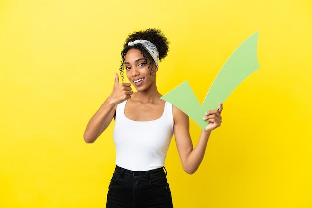 Молодая афро-американская женщина изолирована на желтом фоне, держа значок галочки с большим пальцем вверх