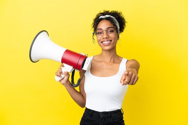 노란색 배경에 격리된 젊은 아프리카계 미국인 여성이 확성기를 들고 앞을 가리키며 웃고 있습니다