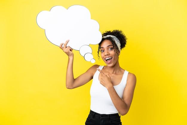 Молодая афро-американская женщина, изолированная на желтом фоне, держит мыслящий речевой пузырь с удивленным выражением лица