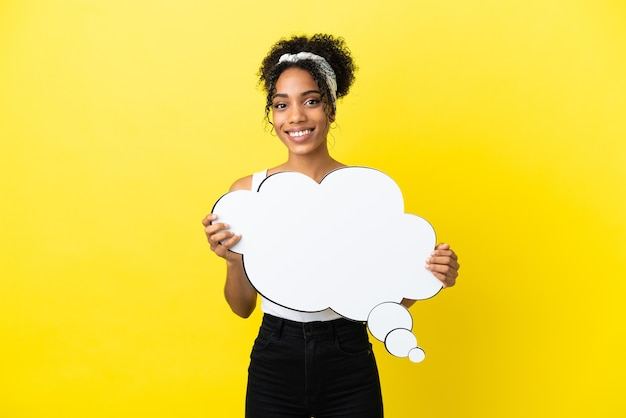 Молодая афро-американская женщина изолирована на желтом фоне, держа мысленный речевой пузырь