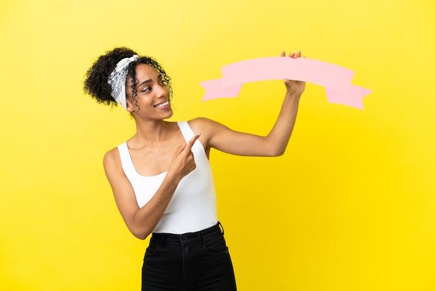 空のプラカードを保持し、それを指している黄色の背景に分離された若いアフリカ系アメリカ人女性