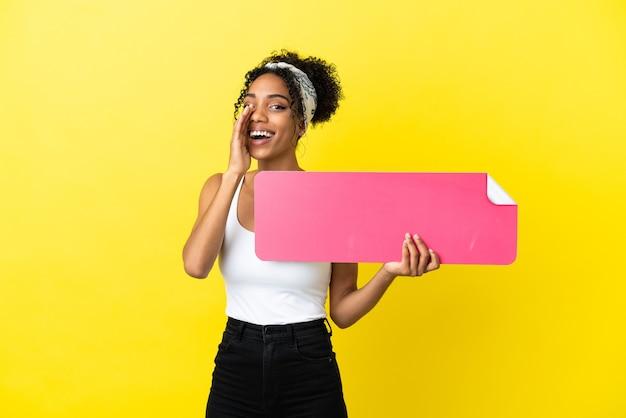 Молодая афро-американская женщина, изолированная на желтом фоне, держит пустой плакат и кричит