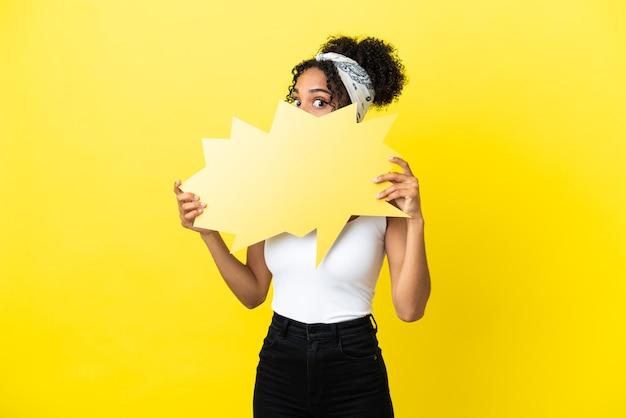 Молодая афро-американская женщина изолирована на желтом фоне, держа пустой речевой пузырь и прячась за ним