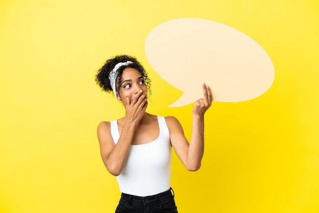 Молодая афро-американская женщина, изолированная на желтом фоне, держит пустой речевой пузырь с удивленным выражением лица