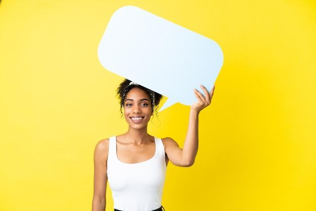 Молодая афро-американская женщина, изолированная на желтом фоне, держит пустой речевой пузырь