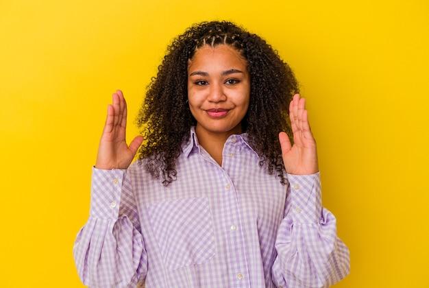 젊은 아프리카 계 미국인 여자는 웃 고 자신감, 집게 손가락으로 뭔가 조금 들고 노란색 배경에 고립.