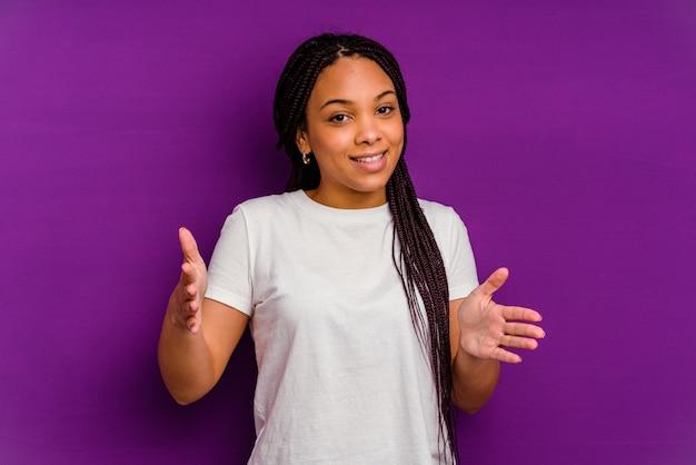 제품 프레 젠 테이 션 양손으로 뭔가 들고 노란색 배경에 고립 된 젊은 아프리카 계 미국인 여자.