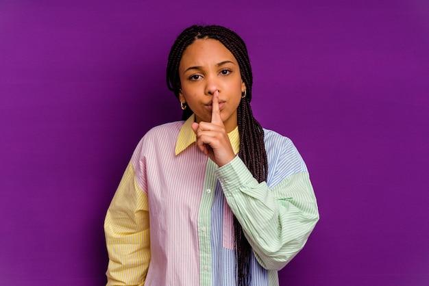 秘密を保持するか、沈黙を求めて黄色の背景に分離された若いアフリカ系アメリカ人の女性。
