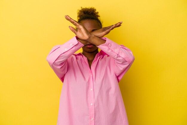 Молодая афро-американская женщина, изолированные на желтом фоне, держа скрещенными руками, концепцию отрицания.