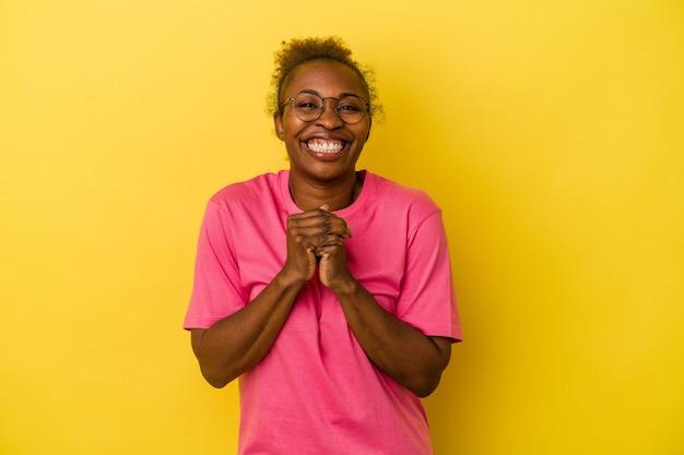 Молодая афро-американская женщина, изолированная на желтом фоне, держит руки под подбородком, счастливо смотрит в сторону.