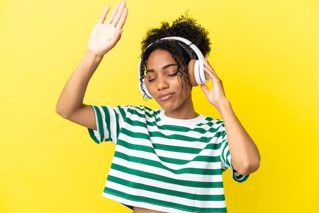 音楽とダンスを聞いて黄色の背景に分離された若いアフリカ系アメリカ人女性