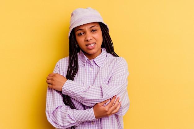ひじをマッサージし、悪い動きの後に苦しんで、黄色の背景に分離された若いアフリカ系アメリカ人の女性。