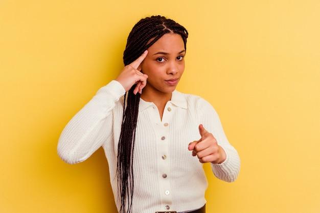 若いアフリカ系アメリカ人の女性は、指で寺院を指して、考えて、タスクに焦点を当てた黄色の背景に分離されました。