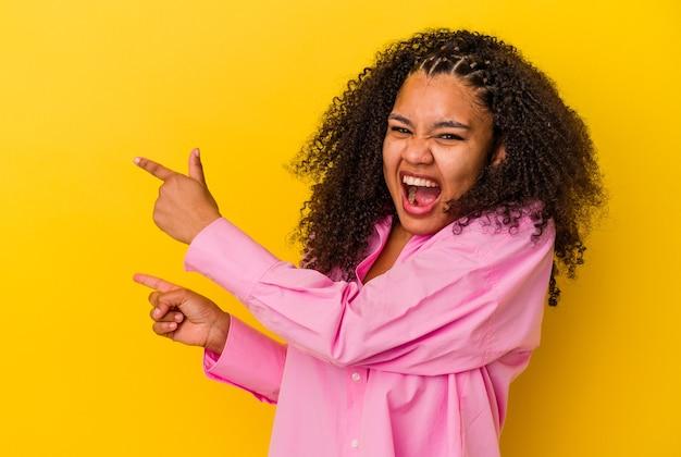 黄色い背景にアフリカ系アメリカ人の若い女性が、人差し指でコピースペースを指し、興奮と欲求を表現している.
