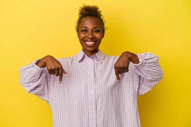 黄色の背景に分離された若いアフリカ系アメリカ人女性は、指で下向き、前向きな気持ちです。