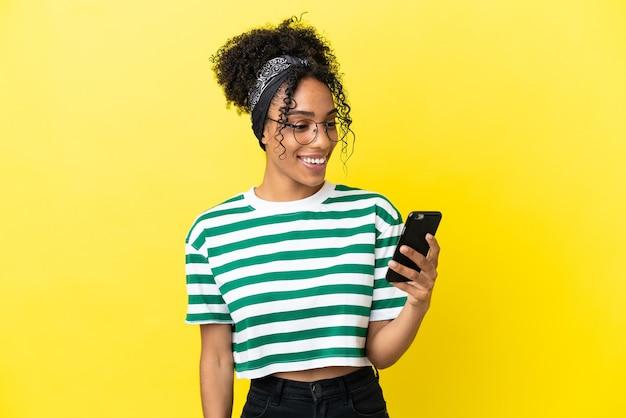 노란색 배경에 격리된 젊은 아프리카계 미국인 여성이 휴대폰으로 메시지나 이메일을 보냅니다.