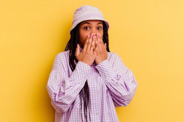 黄色の背景で隔離された若いアフリカ系アメリカ人の女性はショックを受け、手で口を覆い、何か新しいものを発見することを切望しています。