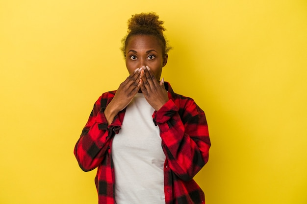노란색 배경에 격리된 젊은 아프리카계 미국인 여성은 손으로 입을 가리고 충격을 받았습니다.
