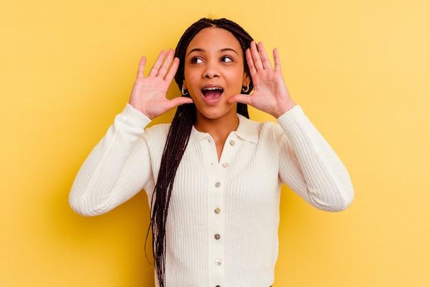 黄色の背景に孤立した若いアフリカ系アメリカ人女性が正面に興奮して叫んでいます。
