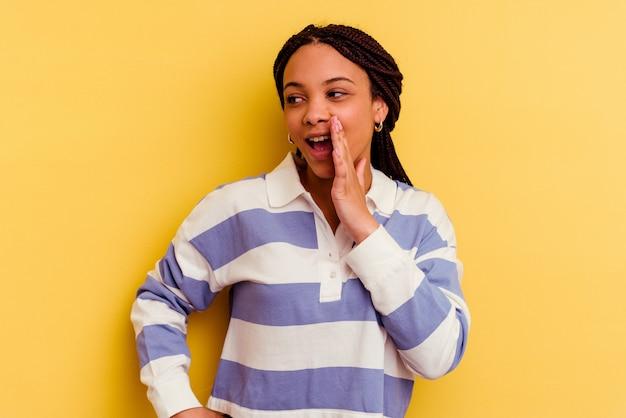 노란색 배경 앞에 흥분 소리에 고립 된 젊은 아프리카 계 미국인 여자.