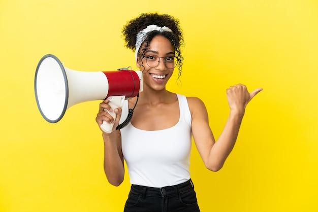 Молодая афро-американская женщина, изолированная на желтом фоне, кричит в мегафон и указывает сторону