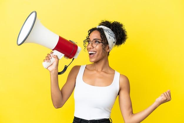 Молодая афро-американская женщина, изолированная на желтом фоне, кричит в мегафон, чтобы объявить что-то в боковом положении