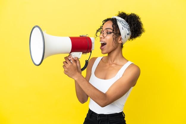 横向きの位置で何かを発表するためにメガホンを介して叫んで黄色の背景に分離された若いアフリカ系アメリカ人の女性