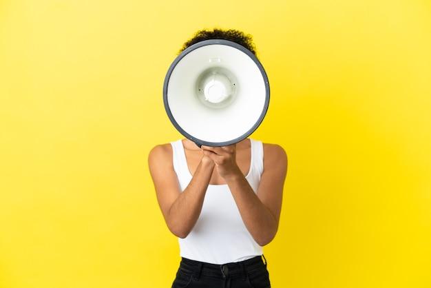 Молодая афро-американская женщина, изолированная на желтом фоне, кричит в мегафон, чтобы что-то объявить