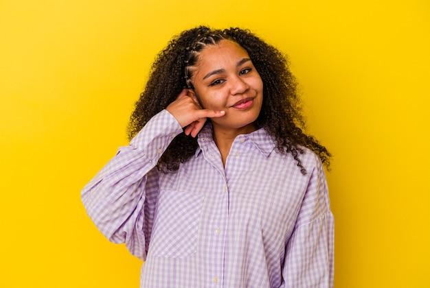 指で携帯電話の呼び出しのジェスチャーを示す黄色の背景に分離された若いアフリカ系アメリカ人女性。