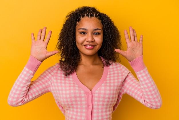 Молодая афро-американская женщина, изолированные на желтом фоне, показывая номер десять руками.