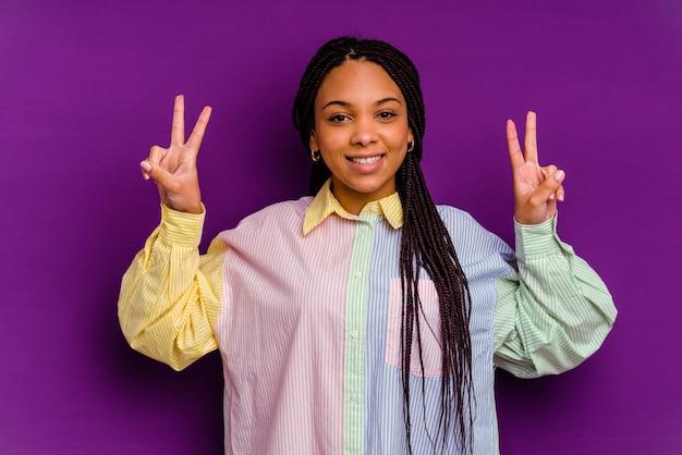 勝利のサインを示し、広く笑顔の黄色の背景に分離された若いアフリカ系アメリカ人女性。