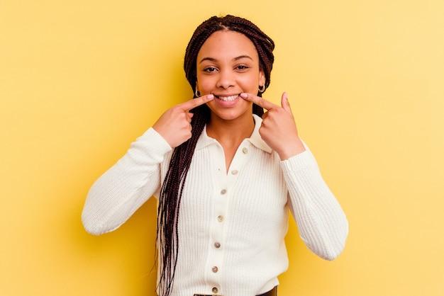 입에 손가락을 가리키는 노란색 배경 미소에 고립 된 젊은 아프리카 계 미국인 여자.