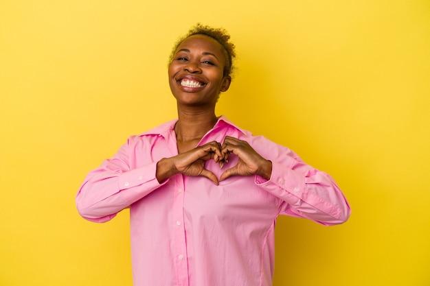 Молодая афро-американская женщина, изолированных на желтом фоне, улыбается и показывает форму сердца руками.