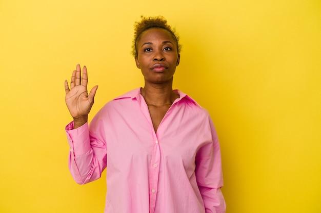 黄色の背景に分離された若いアフリカ系アメリカ人の女性は、指で5番を示して陽気な笑顔を浮かべています。