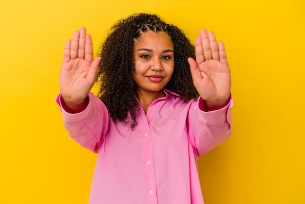 黄色い背景に立っている若いアフリカ系アメリカ人女性が、一時停止の標識を示し、あなたを妨げている差し伸べられた手で立っています。