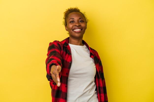挨拶のジェスチャーでカメラで手を伸ばす黄色の背景に分離された若いアフリカ系アメリカ人女性。
