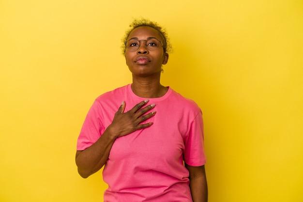노란색 배경에 격리된 젊은 아프리카계 미국인 여성이 가슴에 손을 얹고 맹세합니다.