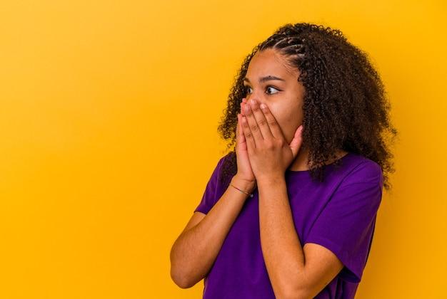 노란색 배경에 고립 된 젊은 아프리카 계 미국인 여자 손으로 입을 덮고 복사 공간을 찾고 사려 깊은.