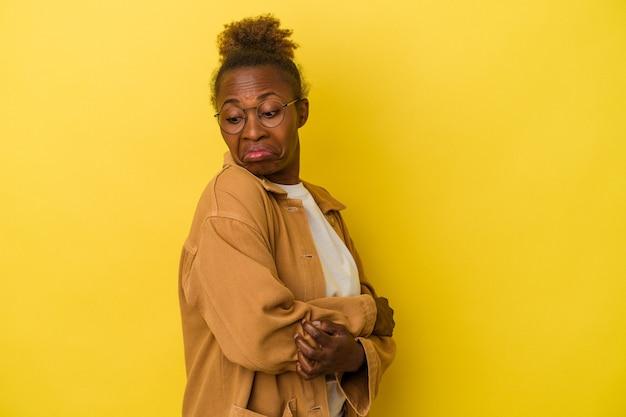 노란색 배경에 고립된 젊은 아프리카계 미국인 여성은 반복적인 작업에 지쳤습니다.