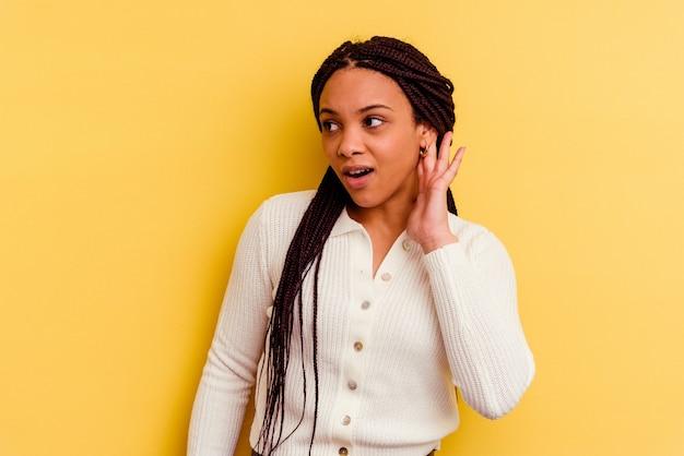 젊은 아프리카 계 미국인 여자는 험담을 듣고 노란색 배경에 고립.