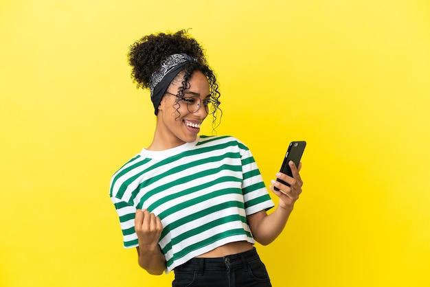 Молодая афро-американская женщина изолирована на желтом фоне с помощью мобильного телефона и делает жест победы
